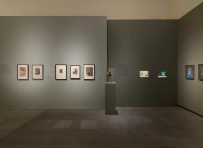 Smaller-scale works on paper on view beside a molded lamp.